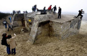 SCHEVENINGEN - Kinderen spelen zaterdag op een bunker in Scheveningen. Deze bunker ziet vanaf zaterdag een maand lang als kunstwerk het levenslicht. Het bouwwerk ligt al decennia lang ingegraven in de duinen. De Franse kunstenaar Cyprien Gaillard liet het bouwwerk voor korte tijd opgraven.